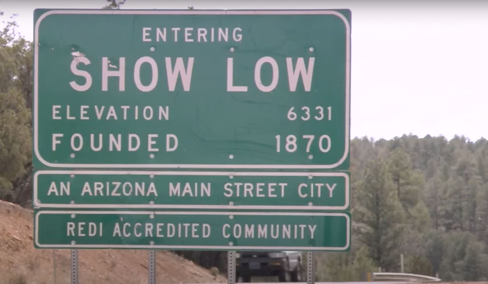 A green sign that says entering Show Low. It lists the elevation and the date Show Low was founded.